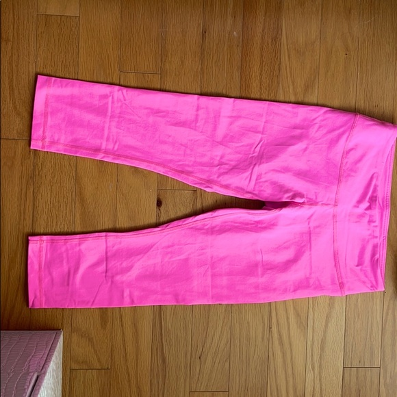 Neon pink Lululemon cropped leggings.